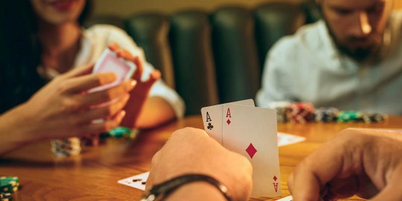Dvi asmeninės kortos žmogaus rankose