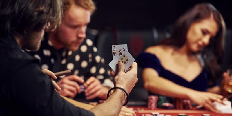 Kortos vieno žaidėjo rankose ir kiti žmonės šalia jo